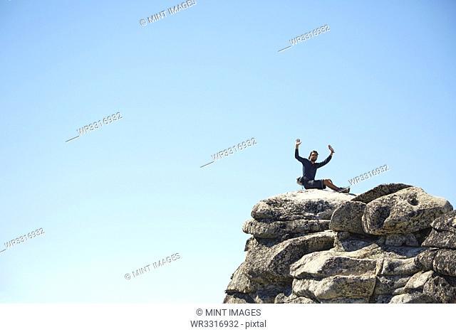 Hiker cheering on rocky hilltop under blue sky