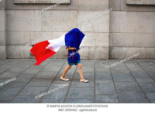 A child playing with the flag of France, celebrating the victory of the national team in the World Cup 2018. Latin Quarter, Paris, France