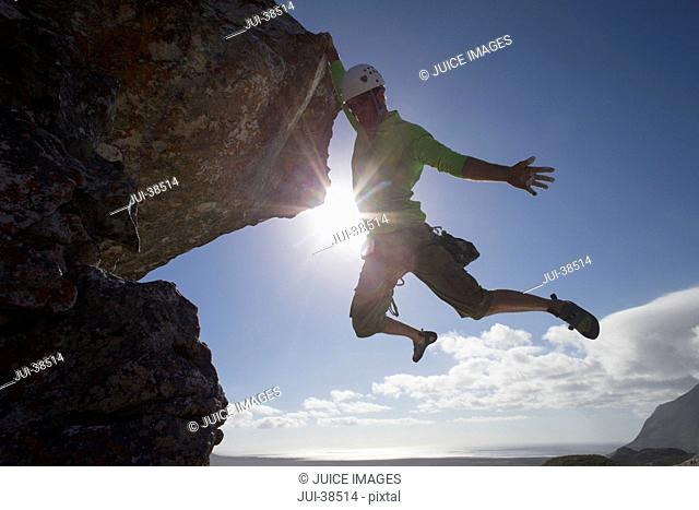 Sun shining behind male rock climber hanging from rock with arm outstretched