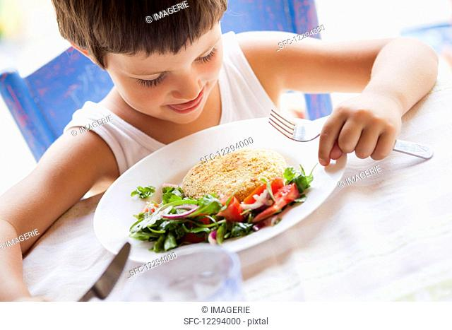 A child eating chickpea patties with salad