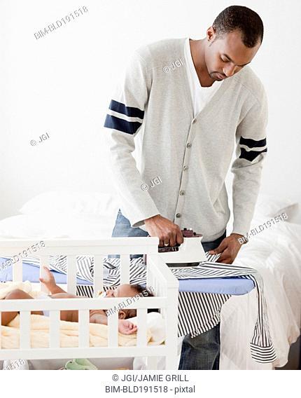 African man ironing shirt near baby in crib