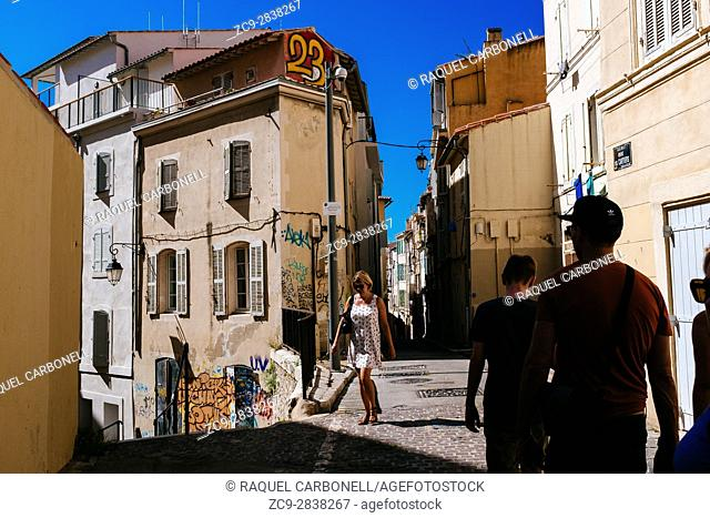 Tourists walking on street between typical houses. Le Panier, Marseille, Provence-Alpes-Cote d'Azur, France