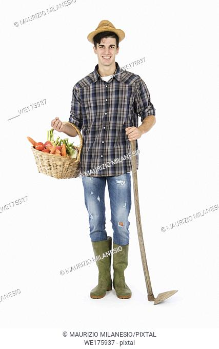 Young farmer holding one arm holding a basket with fruit and vegetables, with the other a hoe, he is wearing a straw hat, checked shirt and green rubber boots