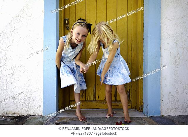 two young candid girls playing and having fun together, outside in front of vintage door. Australian ethnicity
