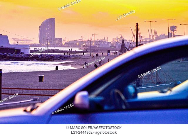 Beach at sunset. First, detail of a blurred car. In the background, beach and Hotel W by Ricardo Bofill architect. Hotel W, aka Vela Hotel