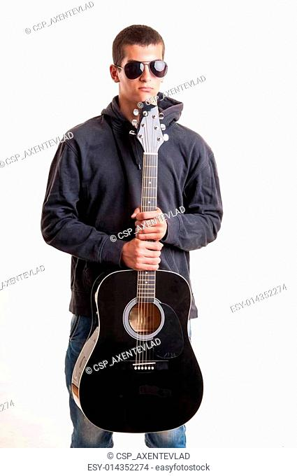 Image of teenager in black clothes, hoodie and sunglasses who is playing at guitar