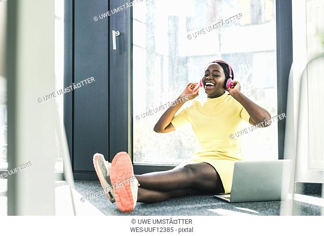 Happy businesswoman sitting on the floor listening to music