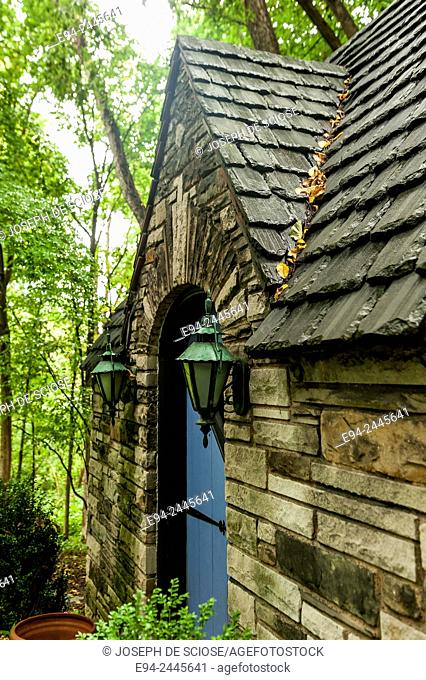 A blue door and a stone cottage with a slate roof in a garden setting. Pittsburgh Pennsylvania USA