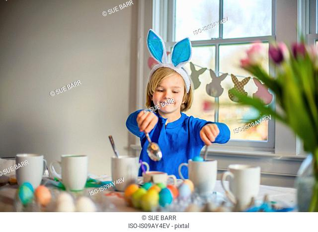 Boy at table wearing bunny ears decorating eggs for Easter