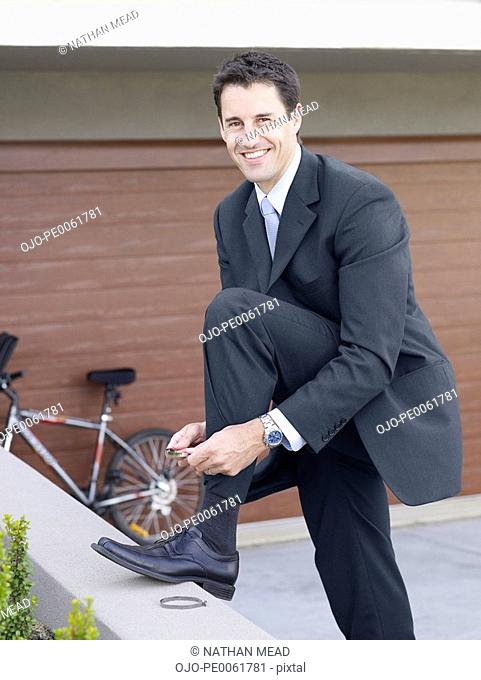 Businessman outdoors putting bicycle clips on his pants
