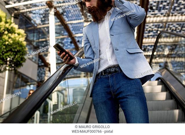 Stylish businessman using cell phone on escalator