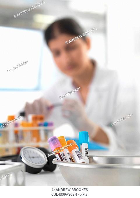 Female doctor preparing blood samples at desk