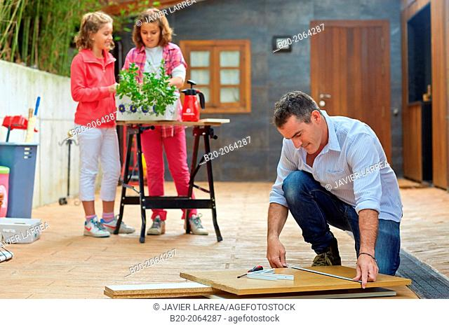 Measuring a wooden board. Tinkering. Father and children doing DIY