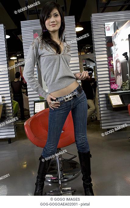 Woman posing by armchair in salon