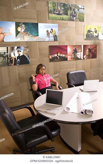 Portrait of young woman sitting alone in conference room