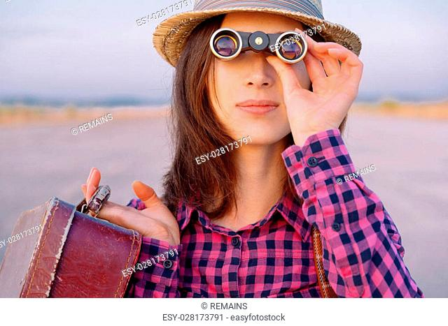 Young hipster woman with suitcase looks through binoculars