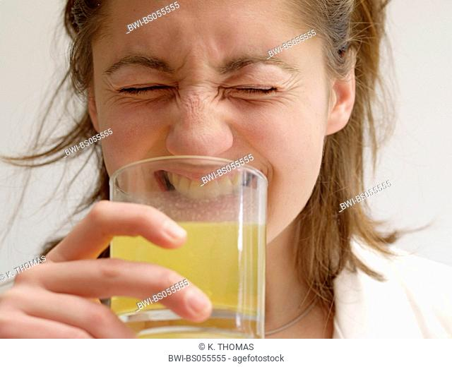 Young Woman / twen, drinking fizzy tablet grimacing with disgust