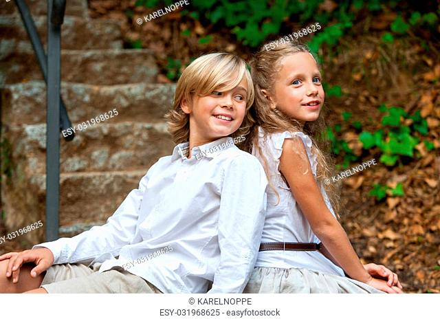 Portrait of cute young couple sitting back to back in park