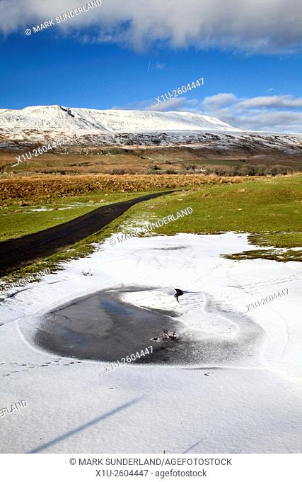 Frozen Pool and Whernside in Winter near Ribblehead Yorkshire Dales England