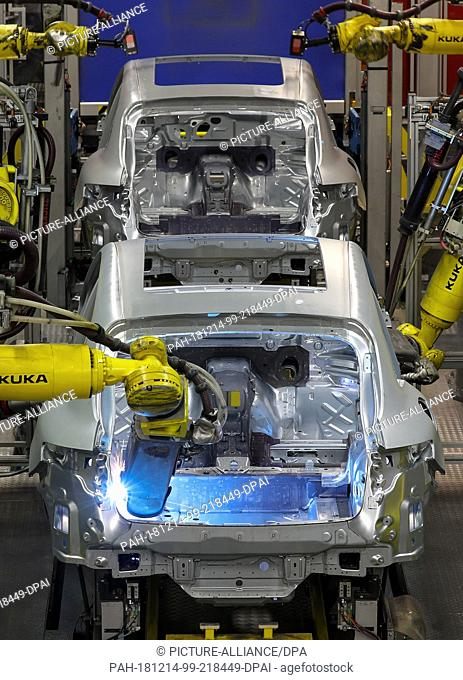 13 December 2018, Saxony, Leipzig: A welding robot places welding spots in the body of a Porsche Macan in the body shop at the Leipzig plant