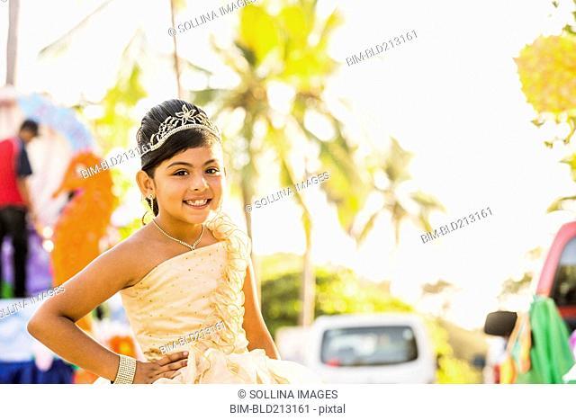 Hispanic girl posing in ornate dress and tiara