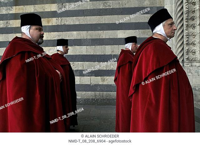 Side profile of four people wearing medieval costume in a historical procession, Orvieto, Umbria, Italy