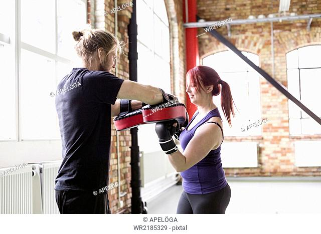 Side view of young woman with male trainer practicing boxing in health club