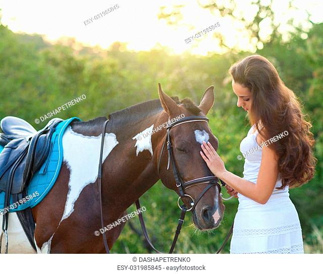 Beautiful woman and a horse. Summer time
