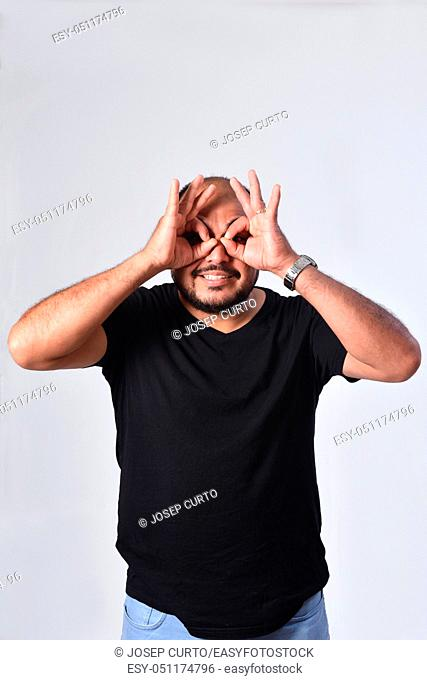 latin american man looking through fingers as if wearing glasses on white background