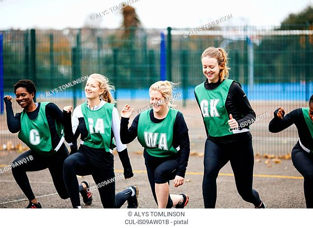 Female netball players warming up on netball court