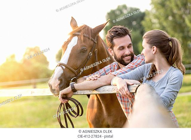 Couple with horse talking at rural pasture fence