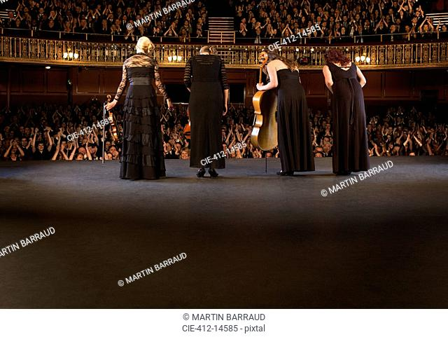Quartet bowing on stage in theater