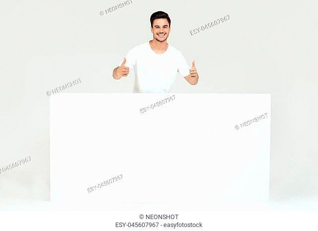 Handsome guy posing with blank white banner, signboard, isolated on white studio background. Happy man looking at camera