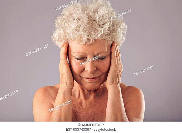 Close-up studio portrait of mature woman in her 70s touching her face against grey background. Old woman examining her skin condition