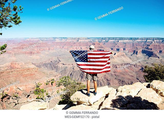 USA, Arizona, back view of man with American flag enjoying view of Grand Canyon National Park