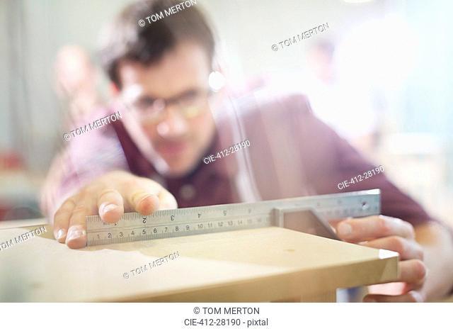 Carpenter measuring wood in workshop