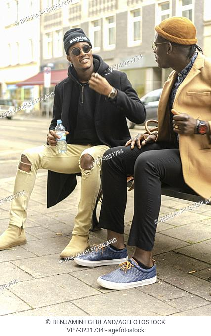 two fashionable young men sitting together on bench at city street, conversation, talking, casual streetstyle fashion, friends, hanging out, in Munich, Germany