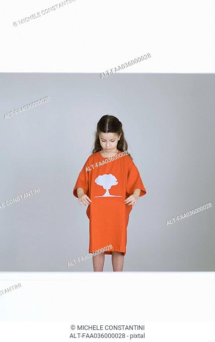 Little girl wearing tee-shirt with mushroom cloud printed on it
