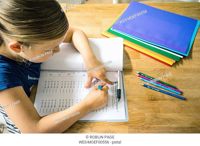 Girl doing homework at table