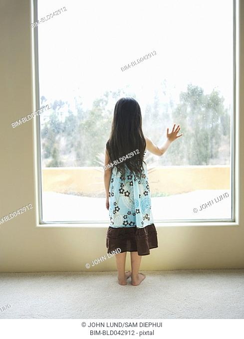 Hispanic girl looking out window