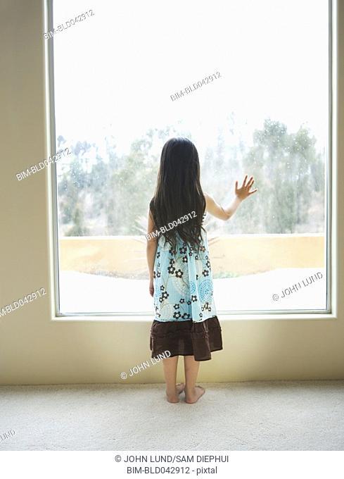 Hispanic girl looking out window