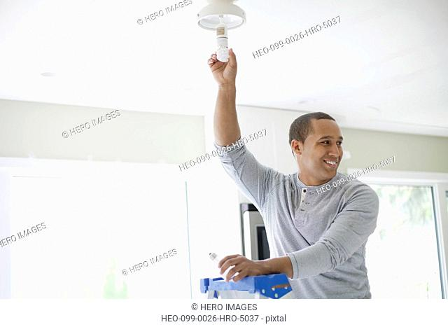 young adult latino man replacing light bulb