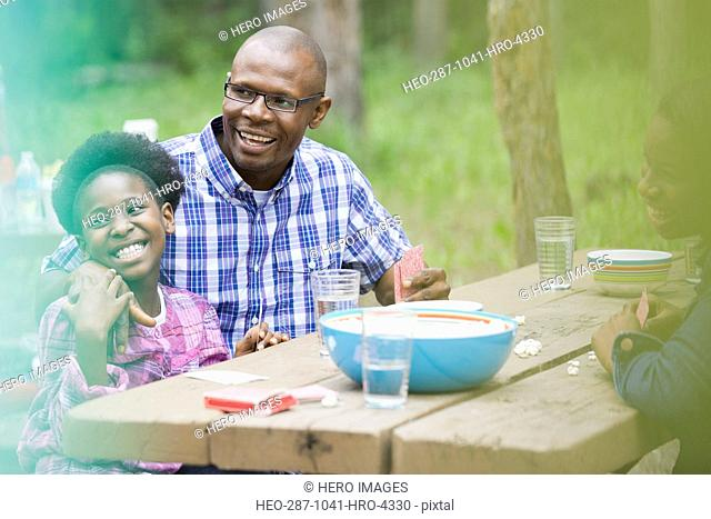Happy father and daughters sitting at picnic table