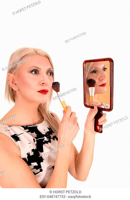 A blond middle age woman holding up a mirror and fixing up her.makeup with a brush, standing in dress, isolated for white background