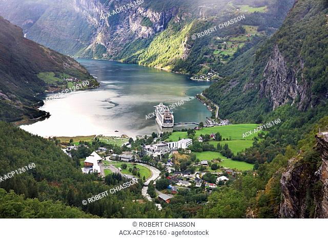 Panoramic view of the village of Geiranger, a cruise ship and the surrounding fjord (Geirangerfjord) as seen from the lookout Flydalsjuvet, Geiranger, Norway