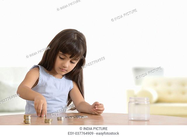 Girl arranging coins on table