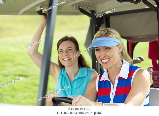 pretty, female golfers driving in golf cart