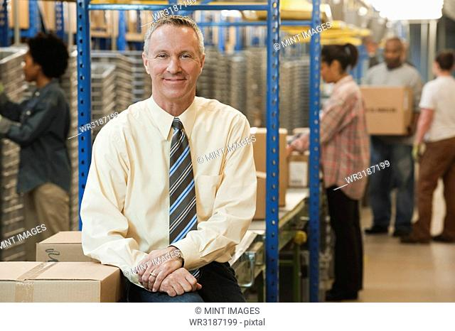 Portrait of a male Caucasian executive in a dress shirt and tie next to a motorized conveyor system in a large distribution warehouse