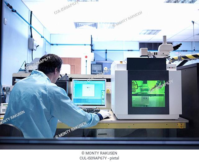 Worker operating laser marking machine in clean room laboratory