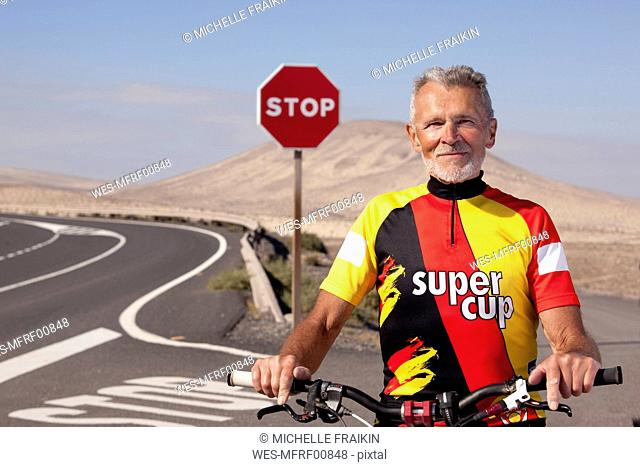 Spain, Canary Islands, Fuerteventura, portrait of confident senior man with mountainbike